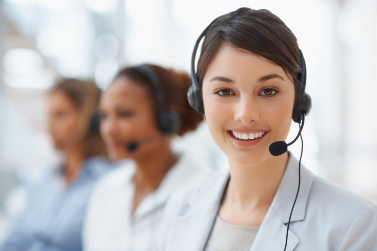 Closeup of a call center employee with headset at workplace